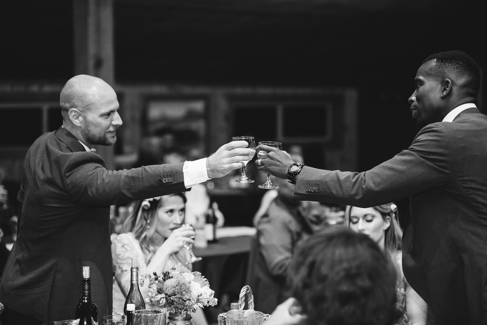 Groom and best man toast black and white reception photography