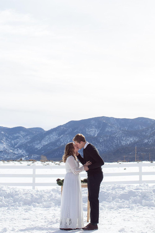 Winter mountain snow wedding first kiss Photographers