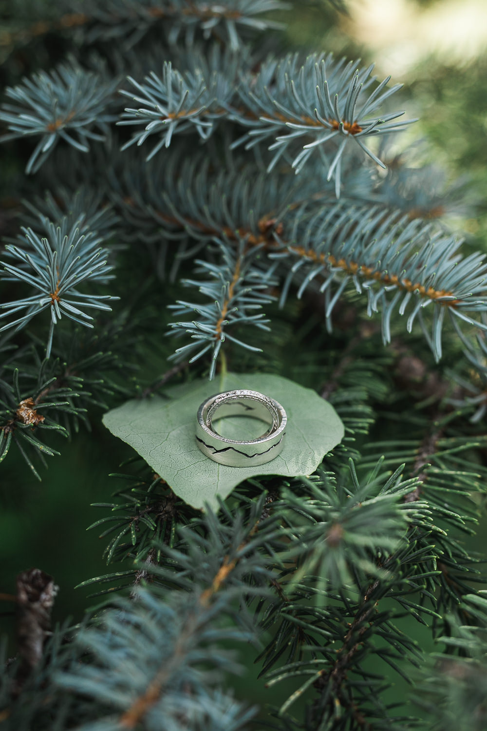 Custom mountain peaks wedding ring pine tree aspen leaf detail photo
