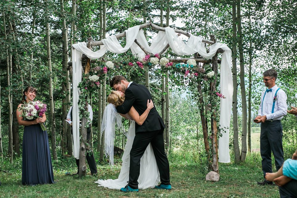 Ceremony first kiss bride and groom durango colorado mountain forest wedding