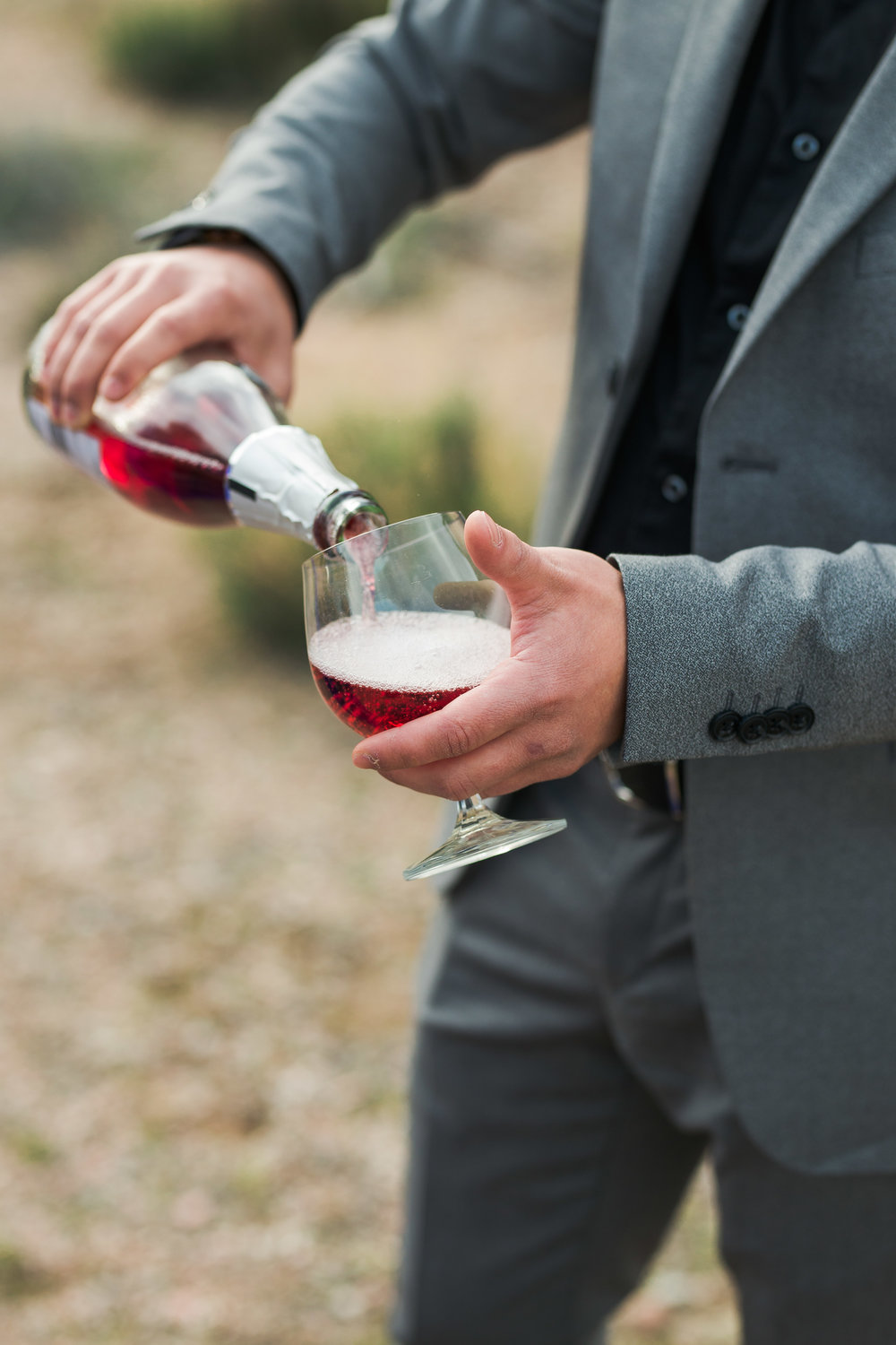 Pouring champagne at a desert elopement among Joshua Trees Kyle Loves Tori Photography