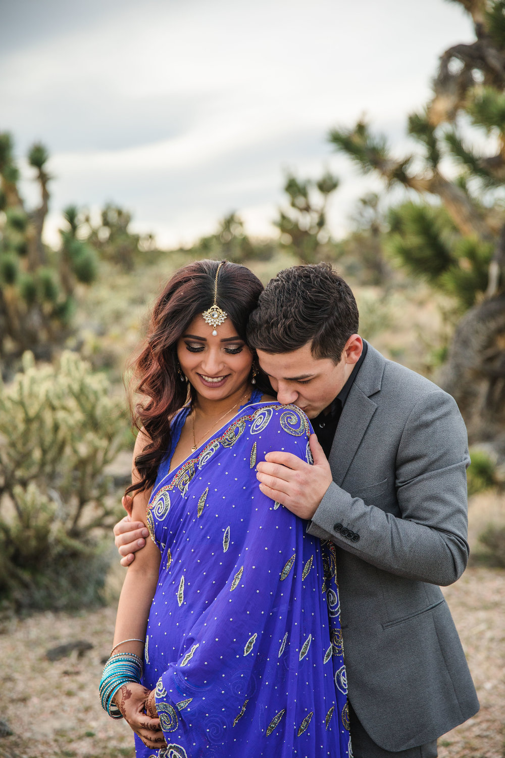 Tender groom kisses his indian bride Desert Adventure Elopement Kyle Loves Tori Photography