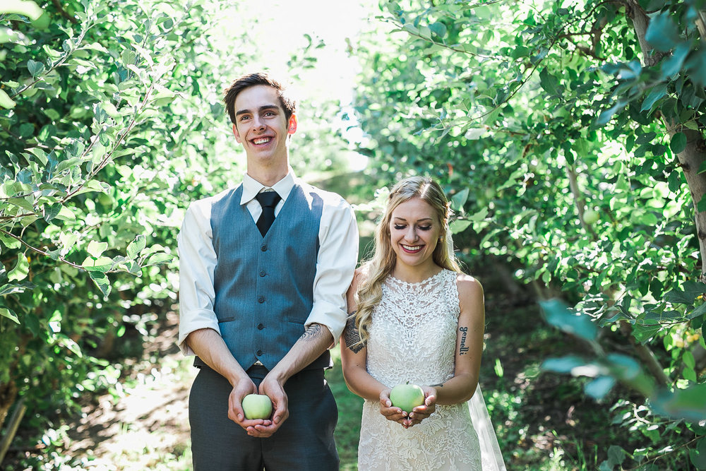 Bride and groom hold apples during their adventure session in a Lake Chelan Washington Winery
