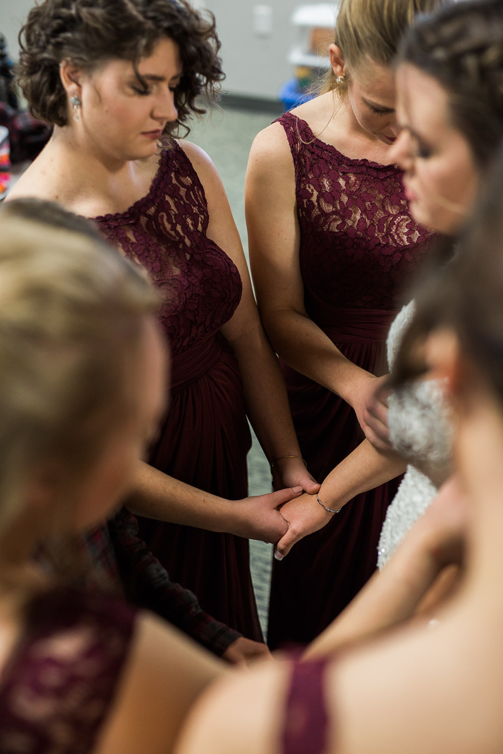 Bridesmaids and mothers pray for bride on wedding day