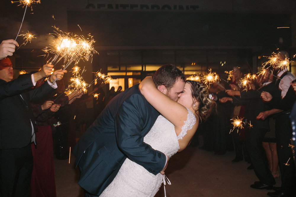 Winter wedding sparkler exit kiss