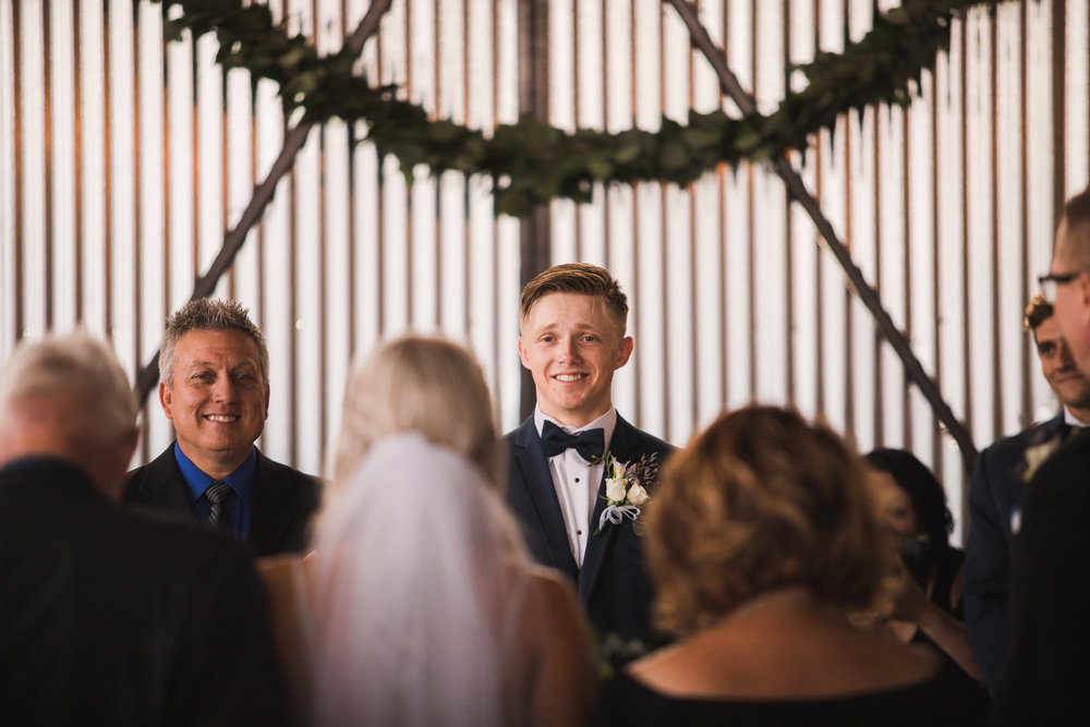 Groom looking at bride as she walks down the isle
