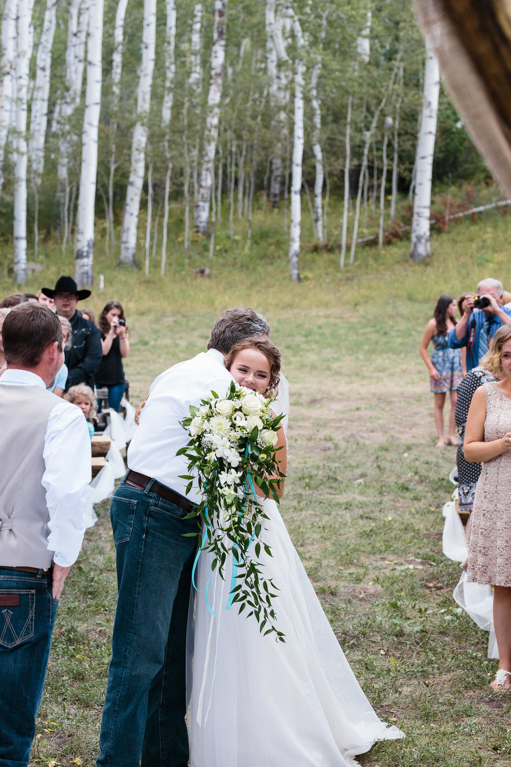 Bride hugs her dad at the ceremony in the Rocky Mountains Colorado