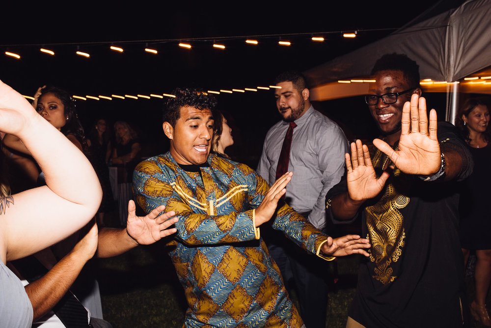 Guests dancing at a wedding reception groomsmen wearing dashikis
