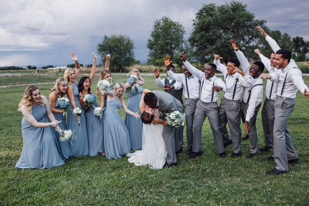 Bridal party excited while bride and groom kiss group portrait