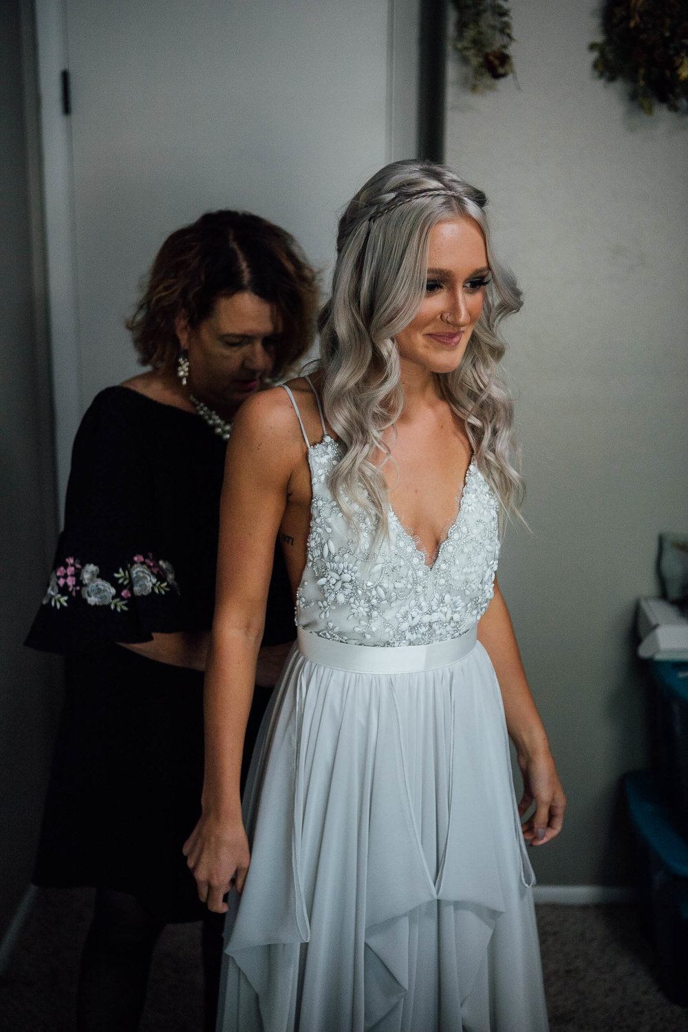 Mother of the bride helping bride put on her wedding dress