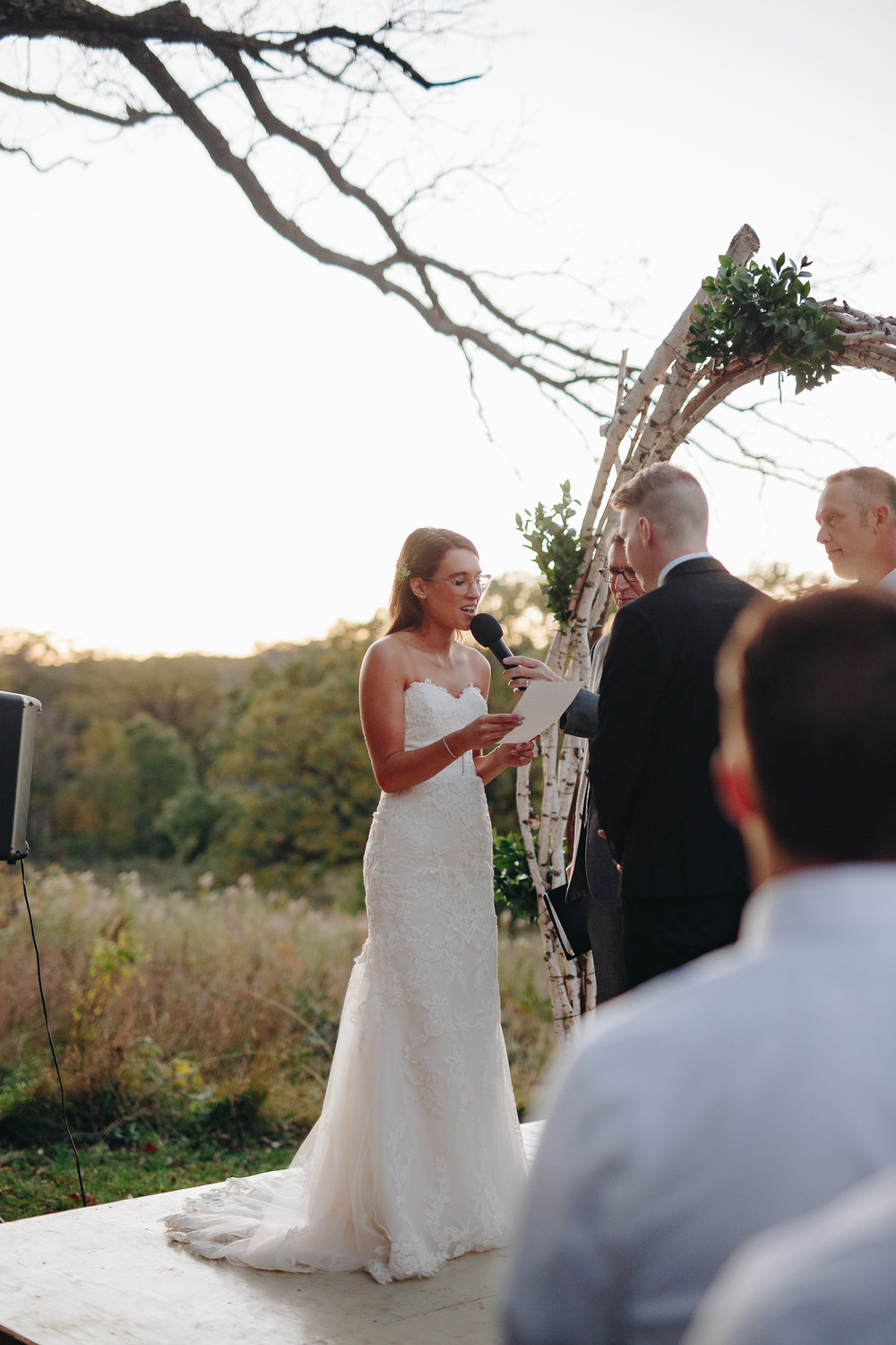Bride reads her vows to her groom at wedding post sunset ceremony