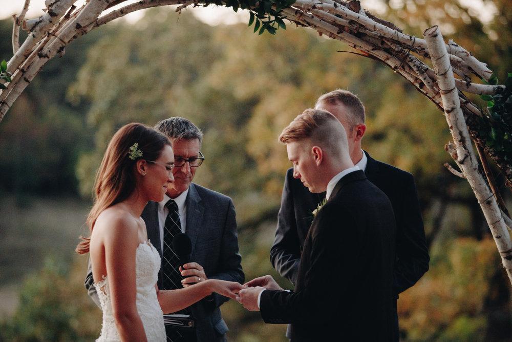 Groom putting ring bride outdoor Minnesota wedding photographers