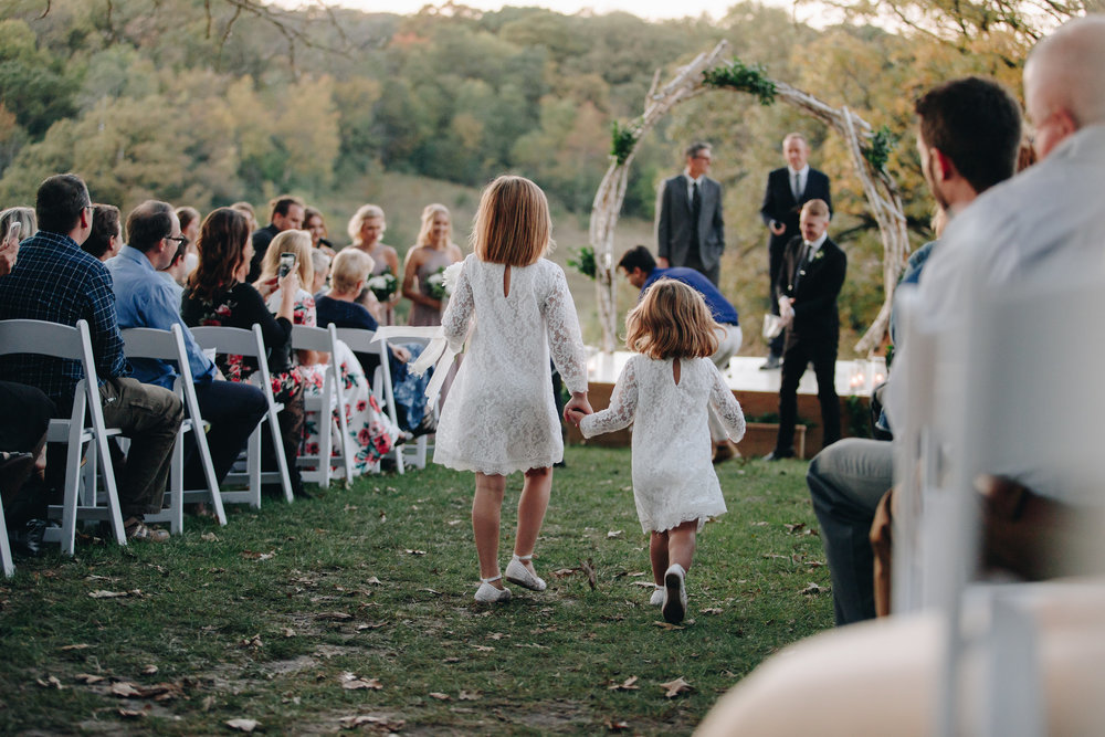 Cute flower girls run down the aisle at outdoor wedding ceremony