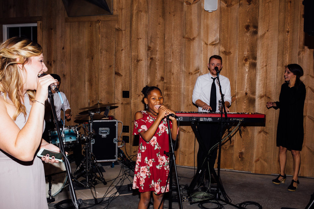 Mother and daughter sing with live band for the bride and groom at wedding reception Almquist Farm Minnesota