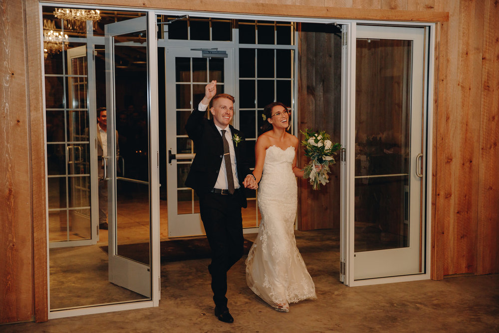 Bride and Groom entrance into modern barnhouse reception at their wedding