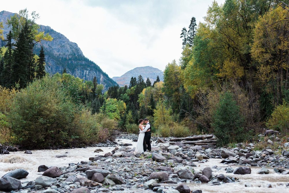 Bride and groom stand near a river in the mountains near Ouray Colorado