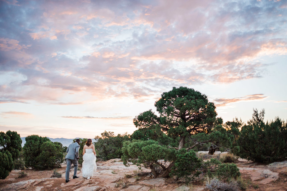 Bride and groom walk together at sunrise in the Colorado National Monument