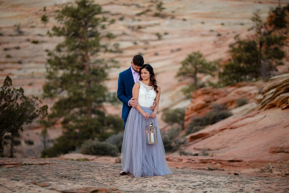 Couple poses holding a lantern in Zion National Park