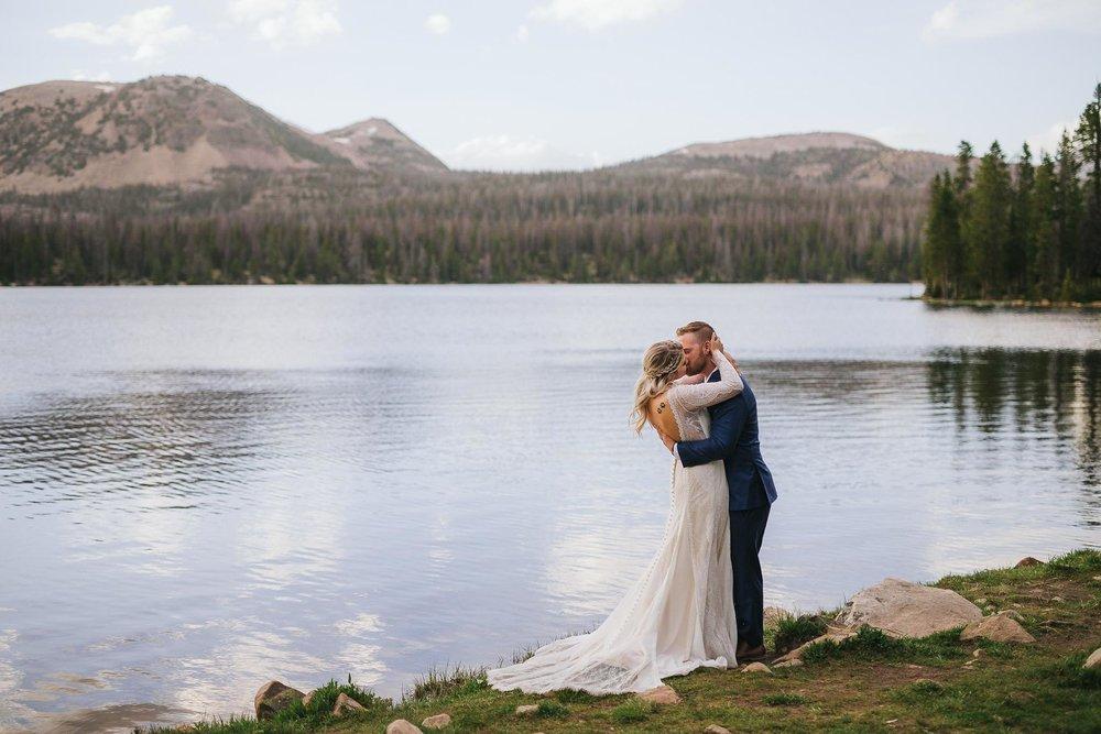 Couple kiss for wedding photos at Mirror Lake in the Utah Uinta Mountains