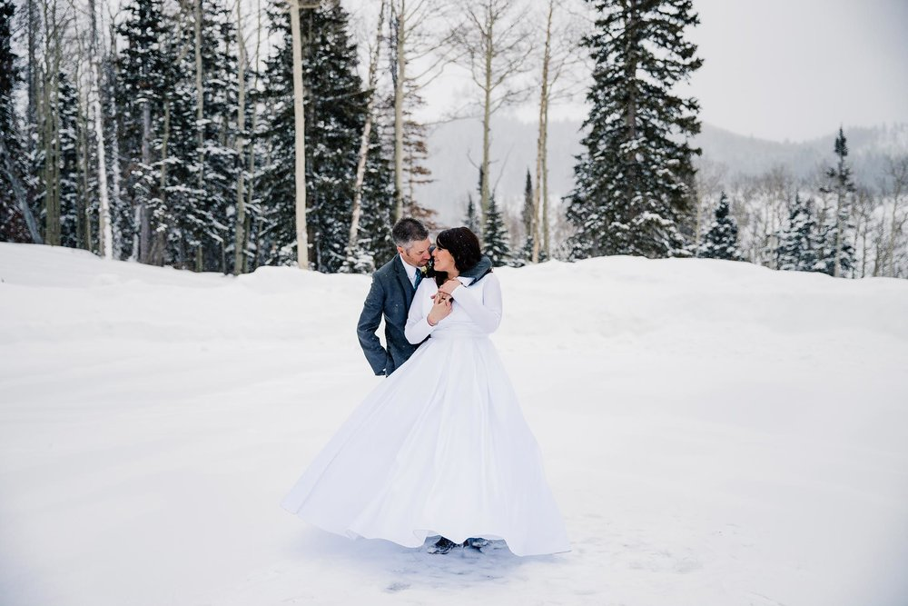 Couple dances in snow at winter wedding at Eagle Mountain Resort, Utah