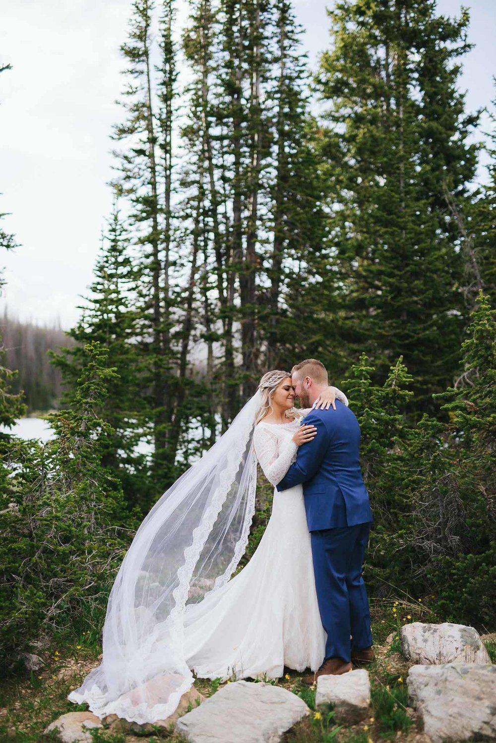 Wedding veil blows in wind while couple hug at Mirror Lake in Utah
