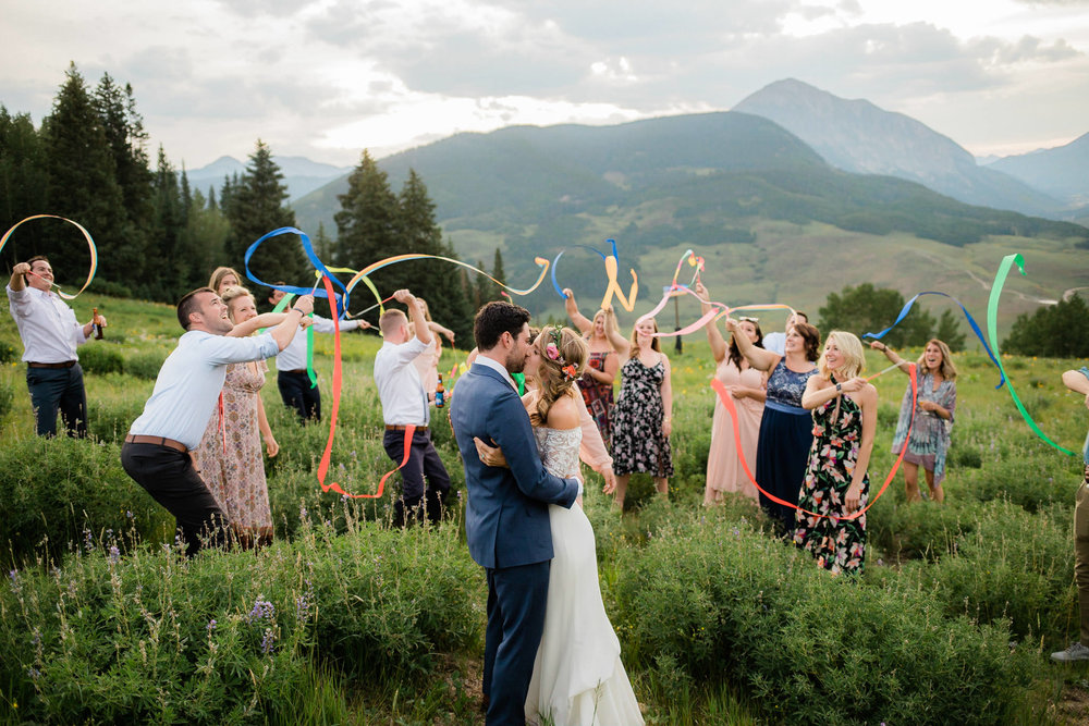 Bride and groom kiss while guests wave ribbons at Crested Butte Resort Ten Peaks in Colorado