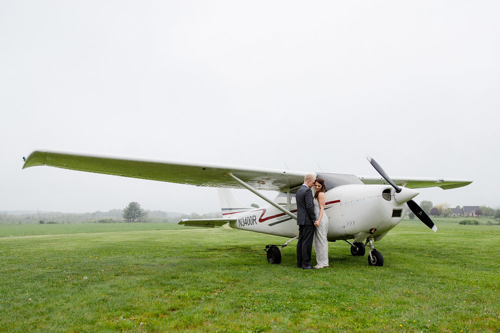 Couple poses by airplane for wedding portraits in Saratoga Springs, New York