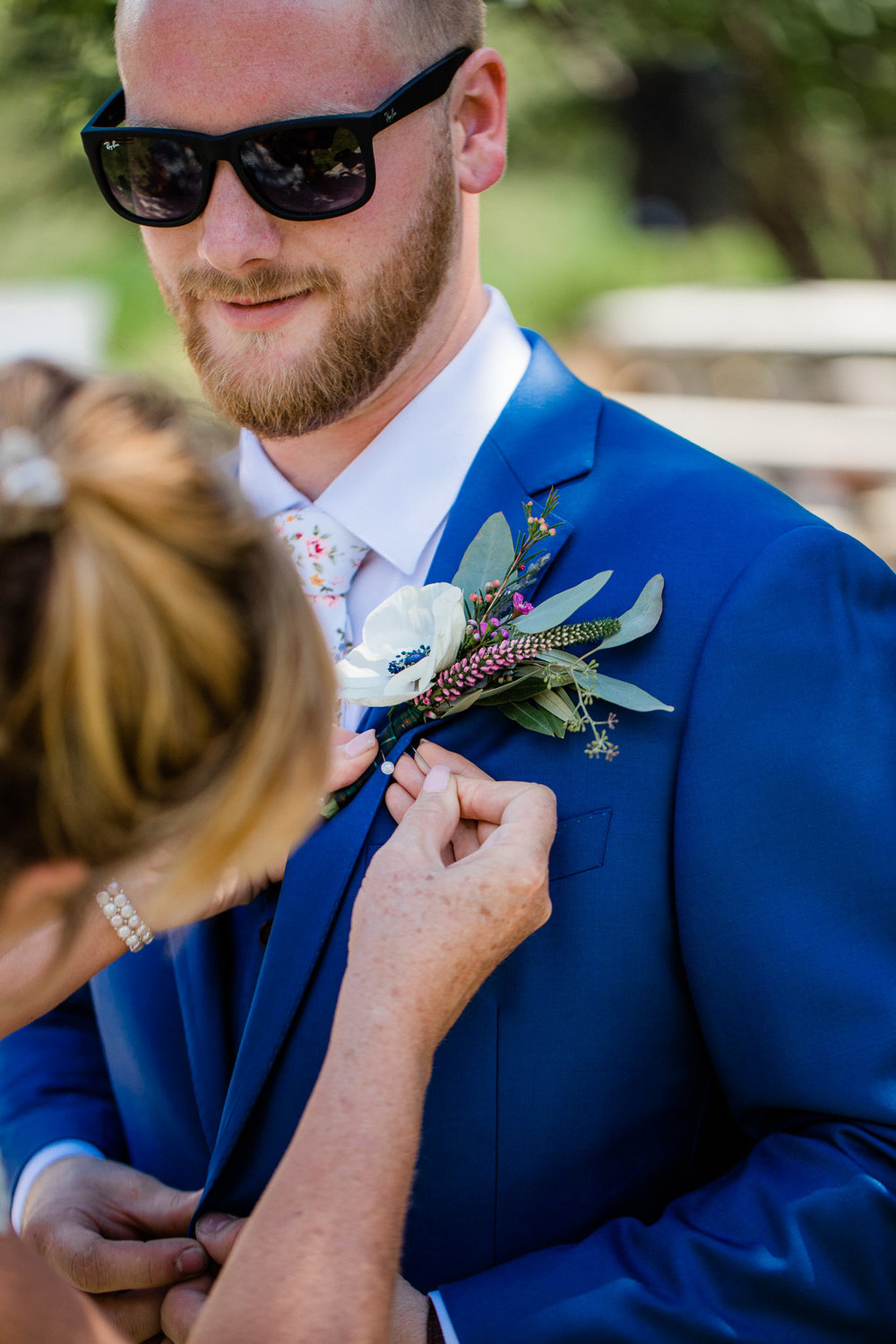 Groom putting on boutonniere on wedding day