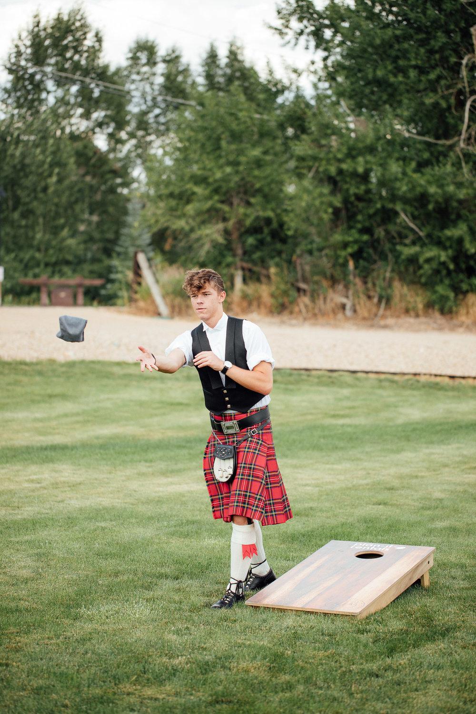 Boy in kilt plays corn hole during wedding reception