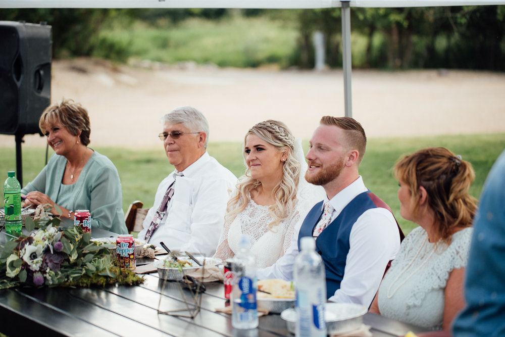Bride and groom listen to toasts during wedding dinner