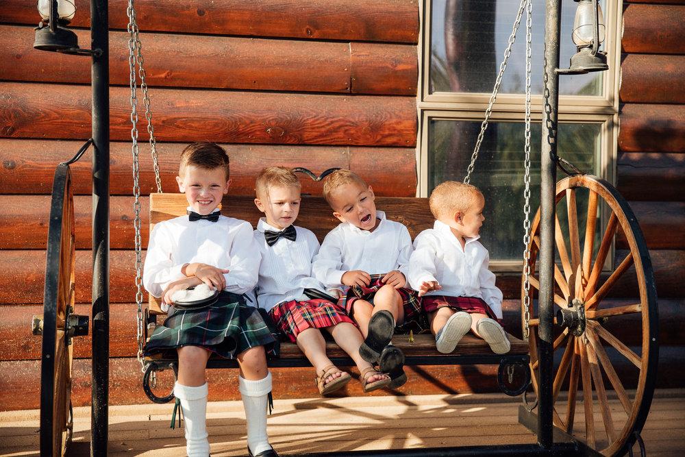 Four little boys in kilts sitting on a swing