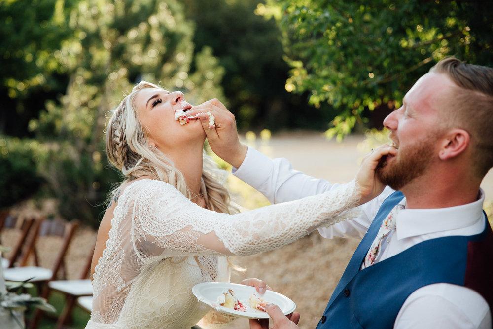 Bride and groom cut cake at wedding reception