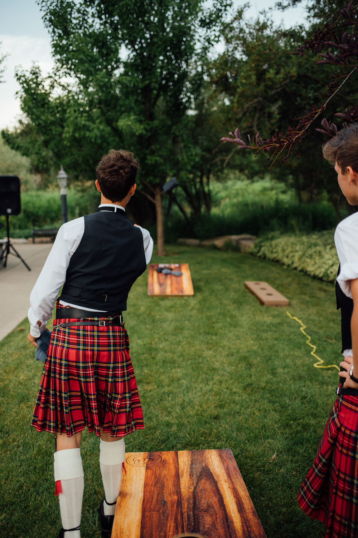 Boy in kilt plays corn hole at wedding reception