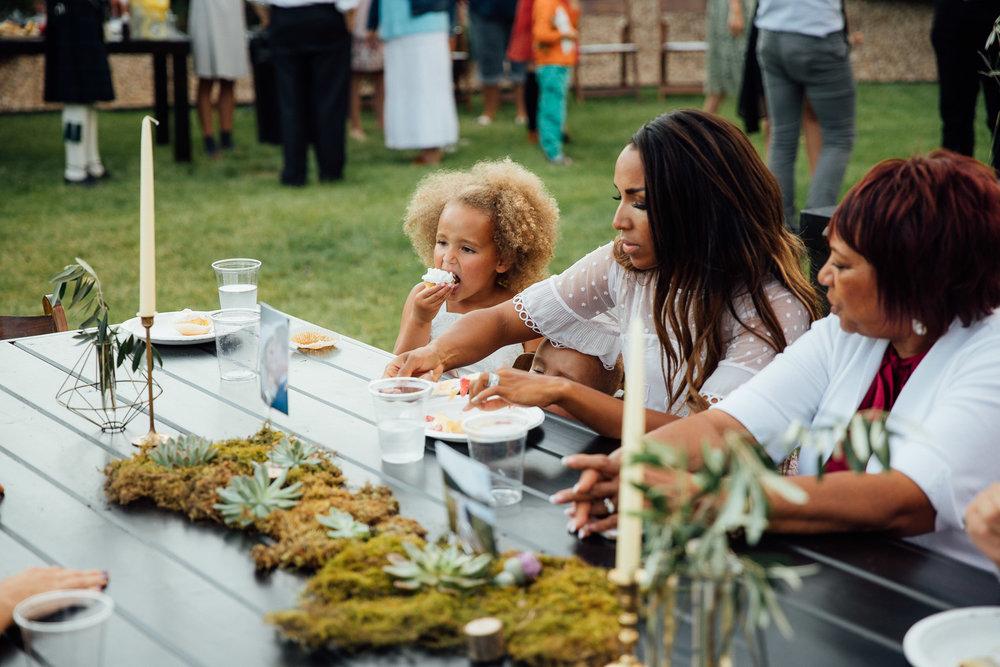 Flower girl eats cupcake at wedding reception