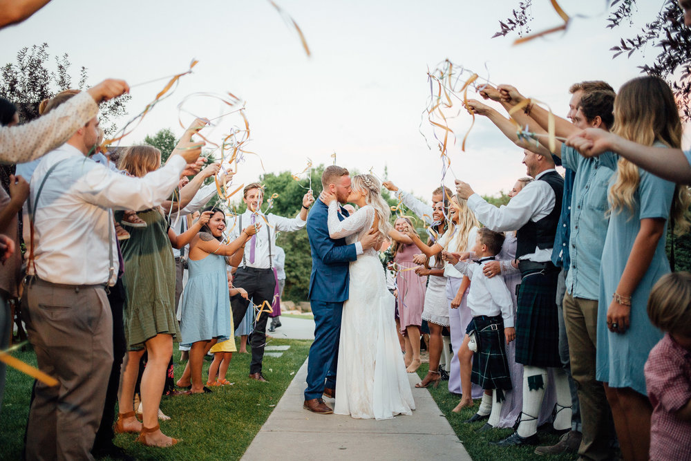 Guests wave ribbons as bride and groom exit wedding reception