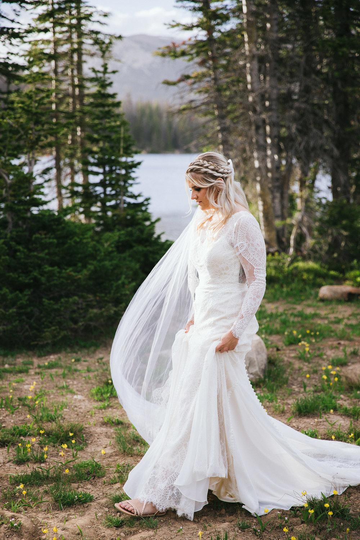 Bride poses for wedding photos at Mirror Lake in the Utah Mountains