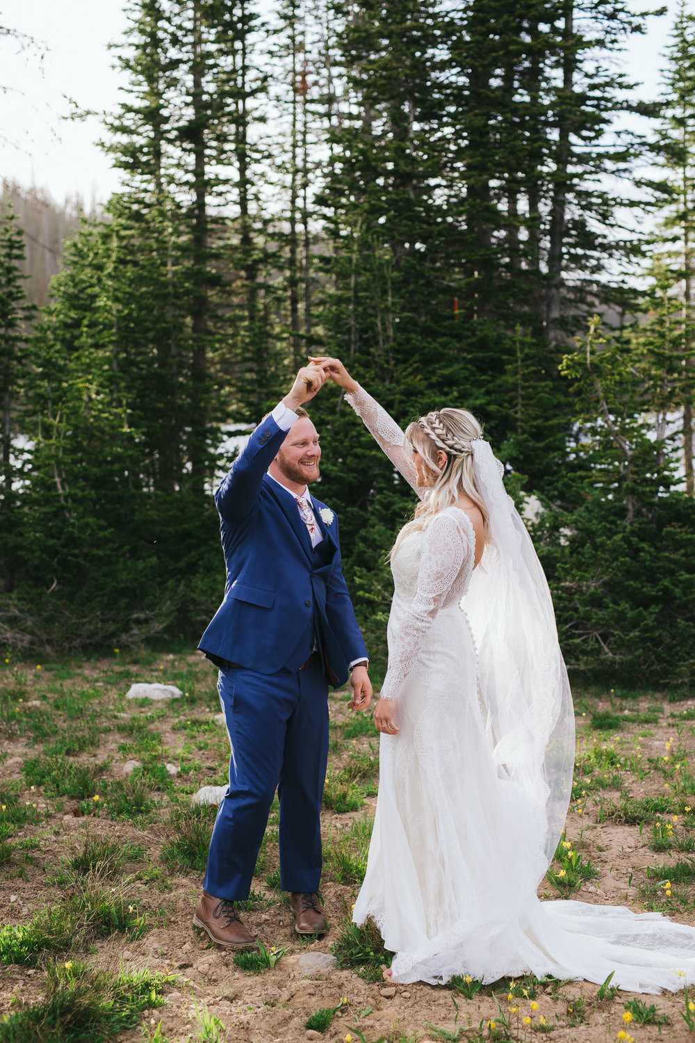 Bride and Groom pose for wedding photos at Mirror Lake in the Utah Mountains
