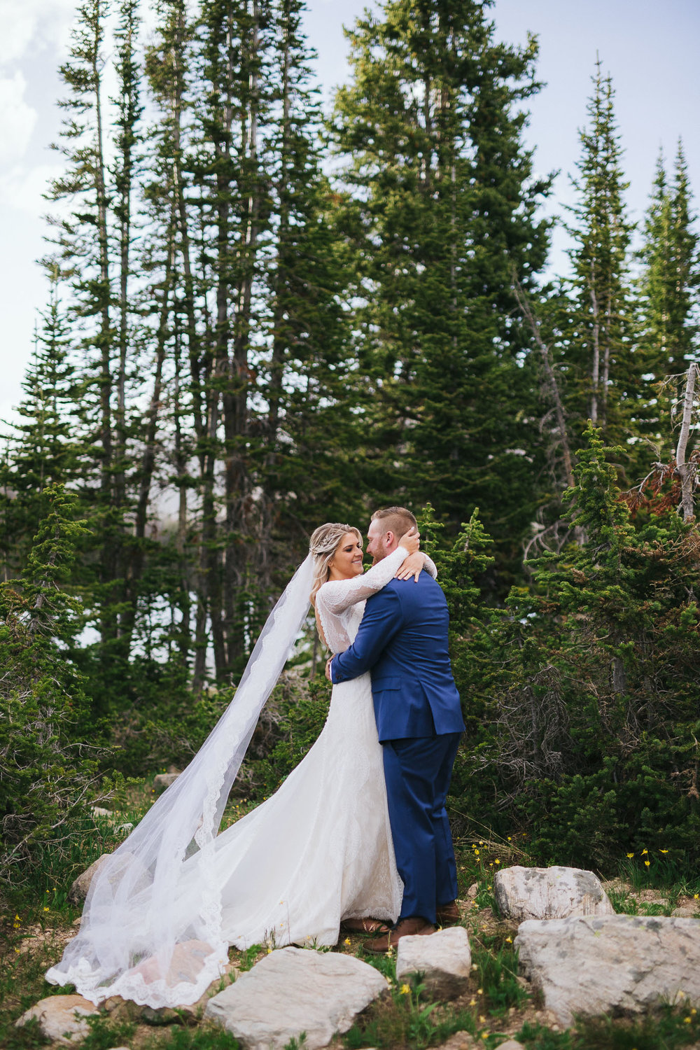 Bride and Groom poses for wedding photos at Mirror Lake in the Utah Mountains