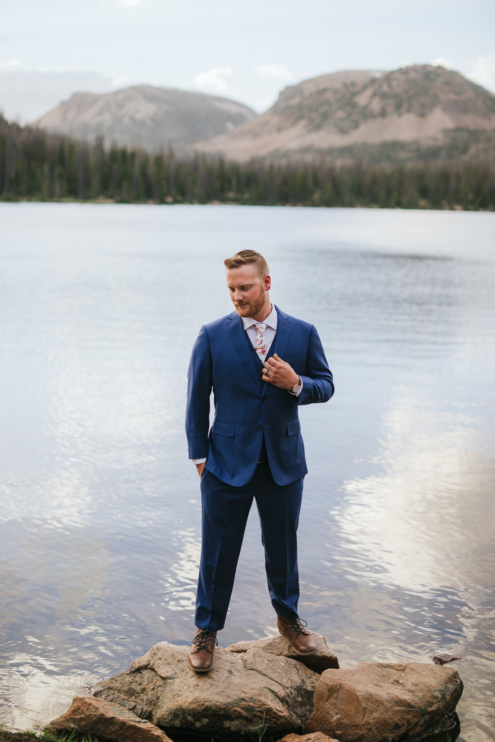 Groom poses for wedding photos at Mirror Lake in the Utah Mountains
