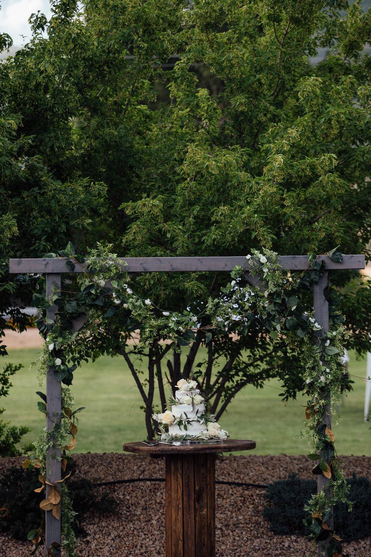 Wedding cake under arbor