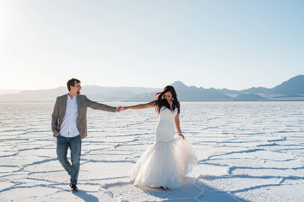Bride and groom walk on the Bonneville Salt Flats during their adventure anniversary session in Utah