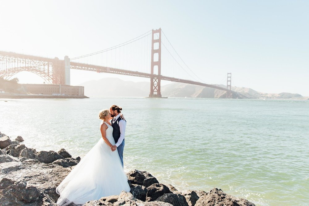 Bride and groom kiss in front of Golden Gate Bridge view during their San Francisco City Hall Elopement