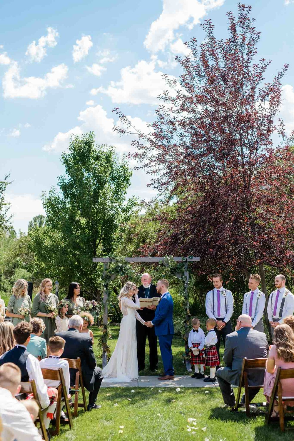 Bride wipes tear from eye Scottish themed wedding ceremony in Midway, Utah