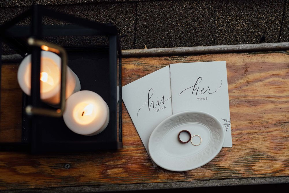 His and her vow books next to candles and dish with wedding rings in New Bedford, Massachusetts