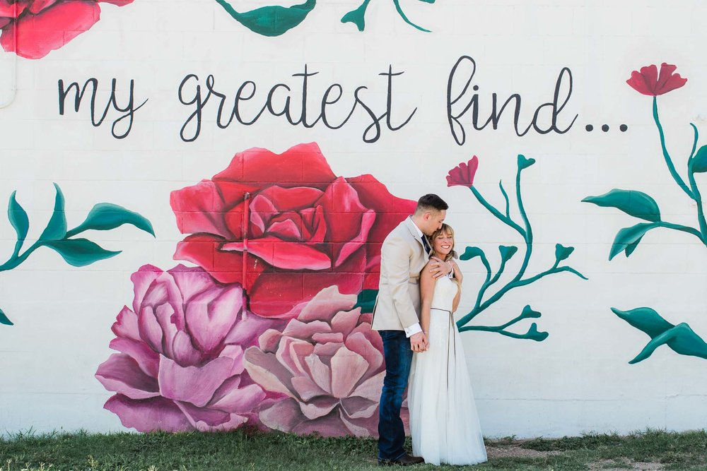 Wedding couple stand in front of My Greatest Find mural in Waco Texas