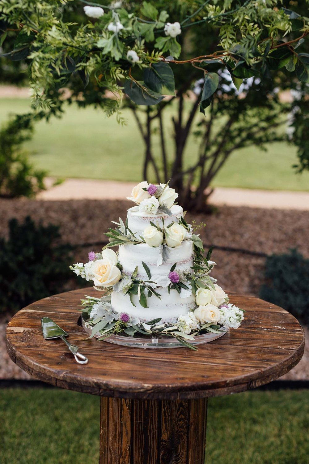 Naked wedding cake with flowers and Scottish thistles at a Midway Utah mountain wedding