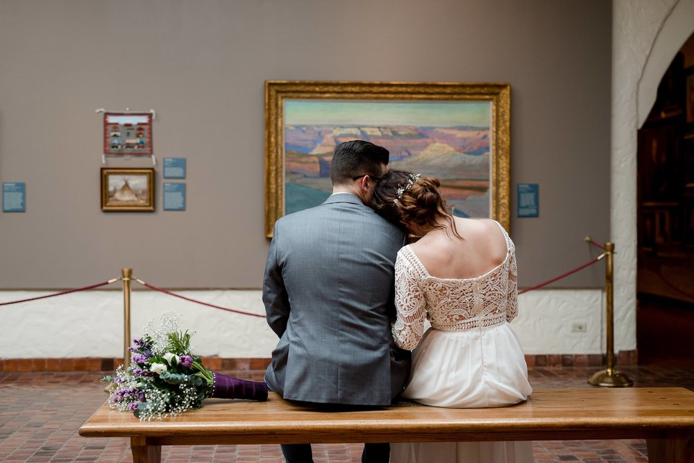 Bride and groom snuggle in front of artwork during their Springville Art Museum Utah wedding photos