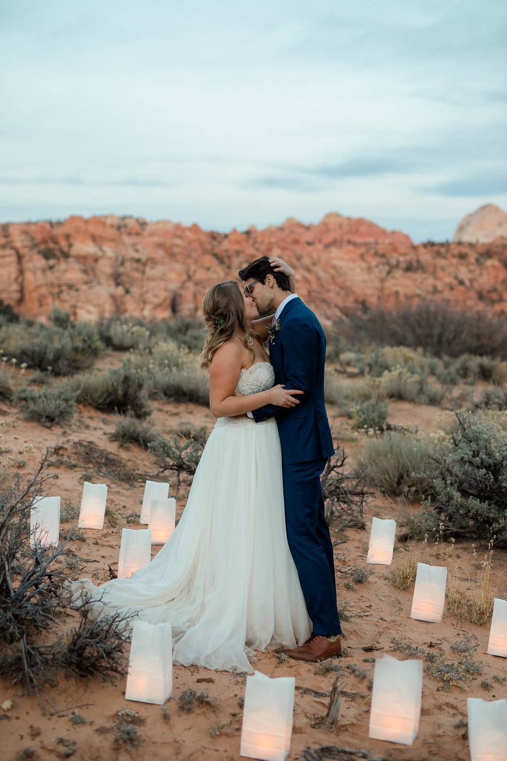 Bride and groom kiss surrounded by lanterns during their intimate adventure wedding in Zion National Park Utah