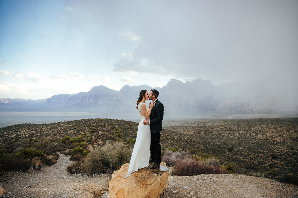 Couple stand on a rock and kiss in a rainstorm during their elopement at Red Rock Canyon, Las Vegas, Nevada