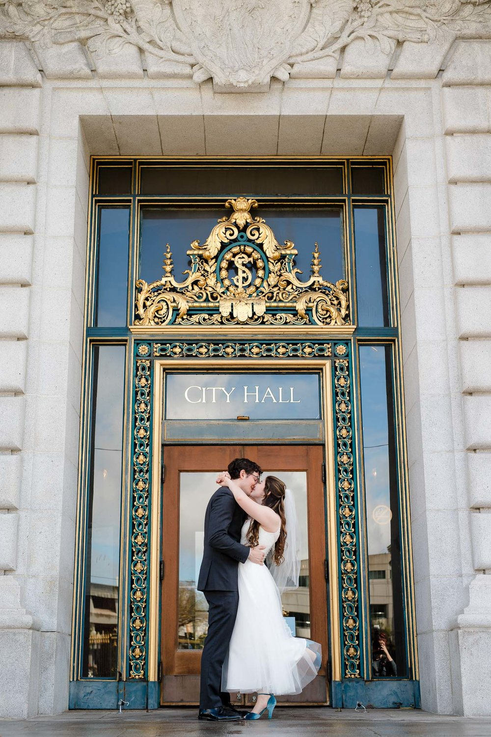 Couple kiss outside San Francisco City Hall doors after their elopement ceremony